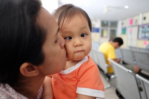 Madre asiatica che trasporta un bambino.