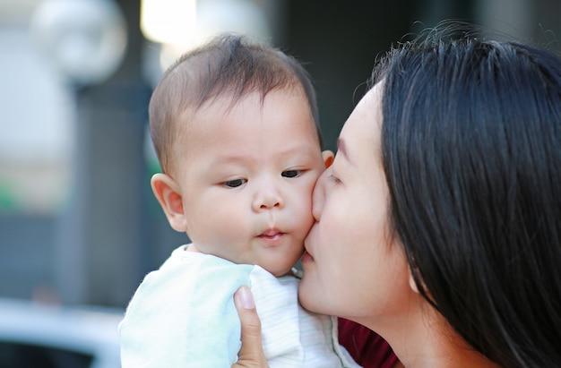 Madre asiatica del primo piano che bacia il suo infante. famiglia felice