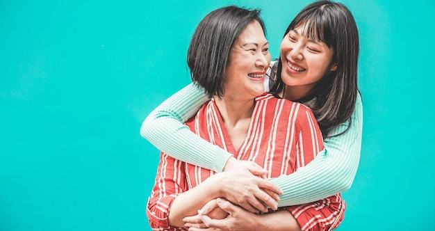 Madre asiatica e figlia che si divertono all'aperto - famiglia felice gente che gode del tempo insieme - amore, stile di vita dei genitori, concetto di momenti teneri - focus sulla faccia della mamma