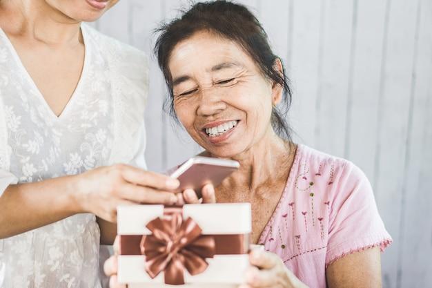 Madre asiatica felice che riceve lo smart phone attuale dalla figlia