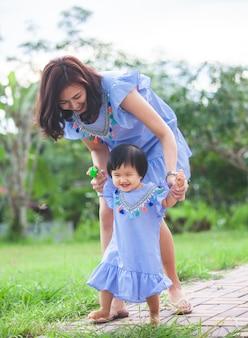 Madre asiatica felice e piccola neonata sveglia che camminano insieme al divertimento e all'amore