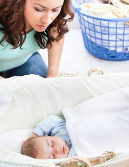 Madre attenta che tiene d'occhio il suo bambino che dorme nella sua culla