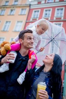 Madre, bambina con ombrello e padre in città