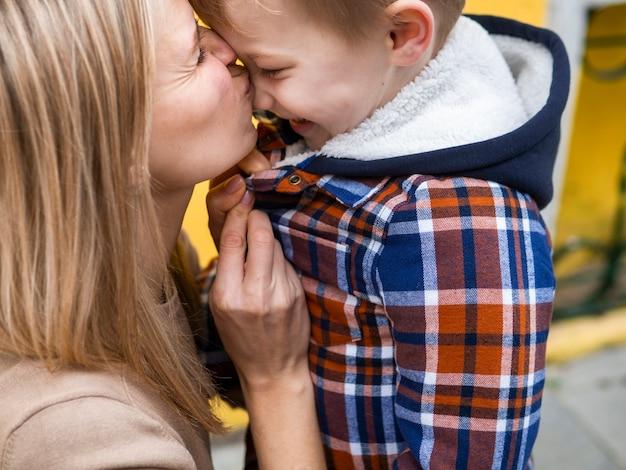 Madre bionda del primo piano che bacia il suo giovane ragazzo
