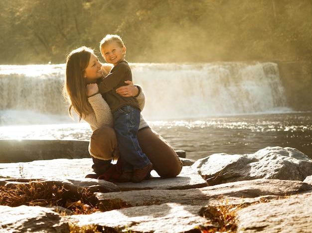 Madre che abbraccia il figlio in un parco immerso nel verde e una cascata sotto la luce del sole