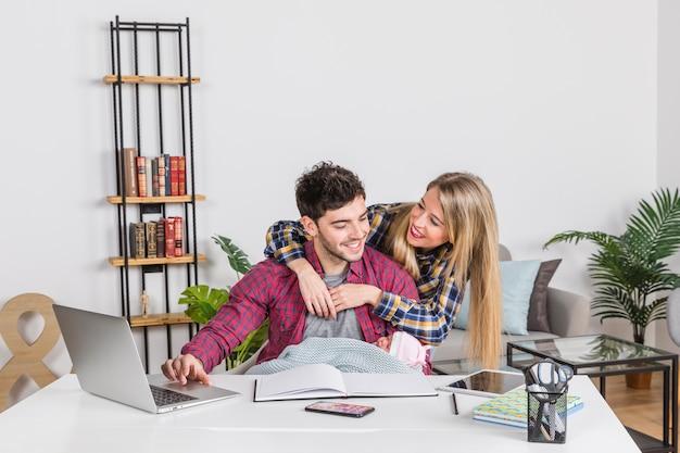 Madre che abbraccia il padre con il bambino alla scrivania