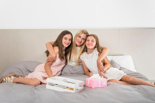 Madre che abbraccia le figlie sul letto vicino al regalo