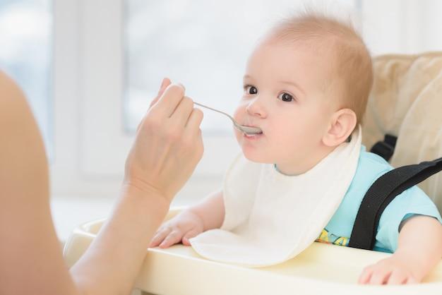 Madre che alimenta il suo giorno del porridge del seno del bambino