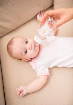 Madre che alimenta la figlia adorabile dalla bottiglia.