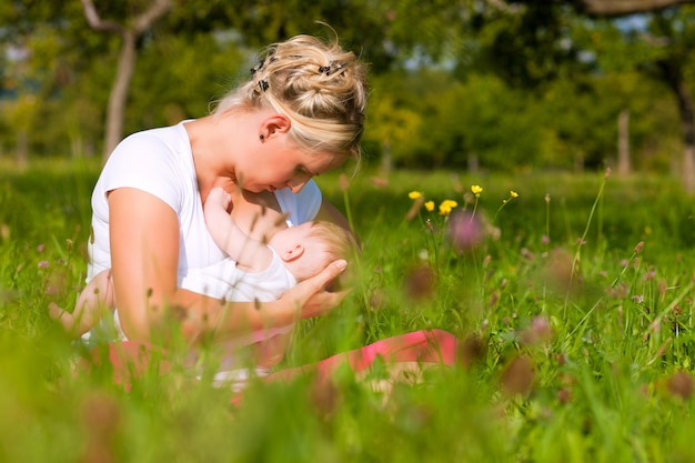 Madre che allatta bambino sul prato