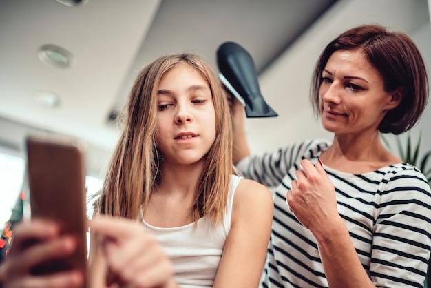 Madre che asciuga i capelli a sua figlia