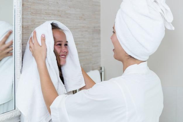 Madre che asciuga i capelli delle sue figlie con un asciugamano