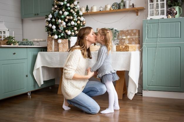 Madre che bacia il suo bambino nella cucina di natale a casa.