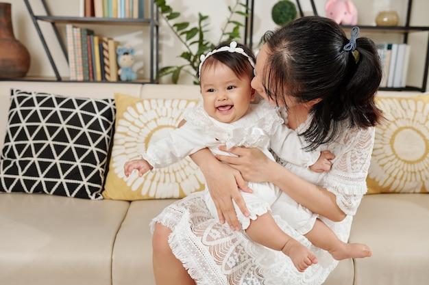 Madre che bacia la piccola figlia sorridente sulla guancia