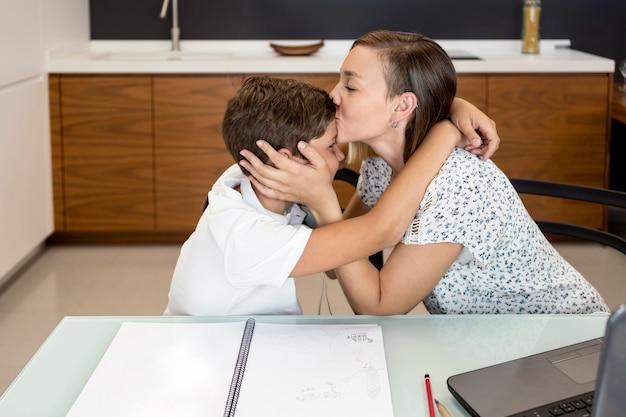Madre che bacia suo figlio per aver finito i compiti