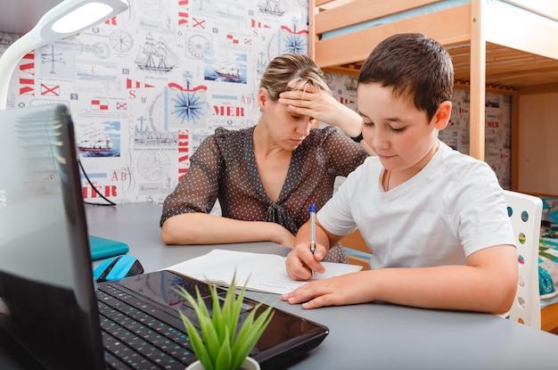 Madre che cerca di parlare con il cliente del lavoro sul computer portatile mentre il bambino resta a casa. homeschooling e apprendimento a distanza.