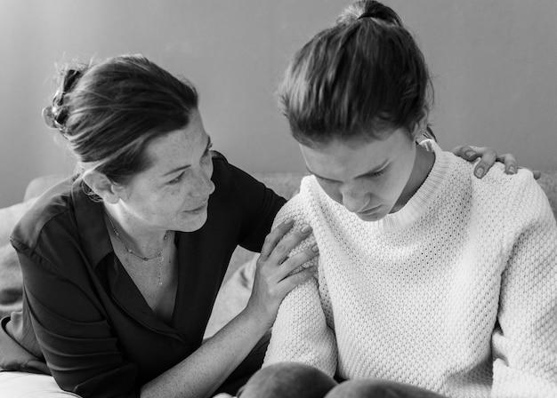 Madre che consola la sua triste figlia