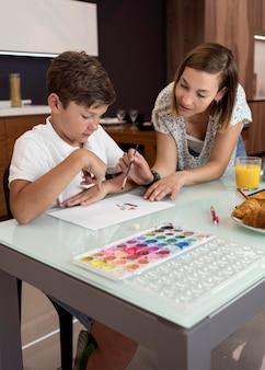 Madre che controlla i figli che dipingono per la scuola