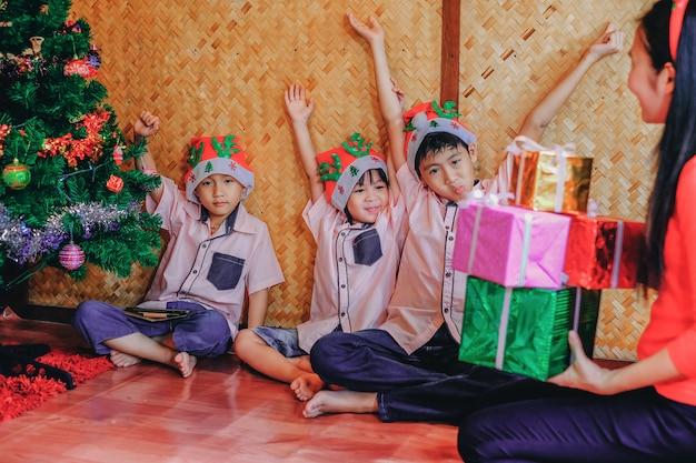 Madre che dà regali ai bambini nel festival di natale.
