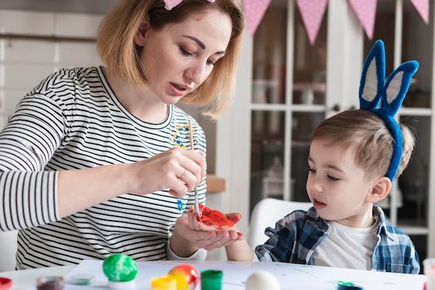 Madre che dipinge la sua mano dei figli per pasqua