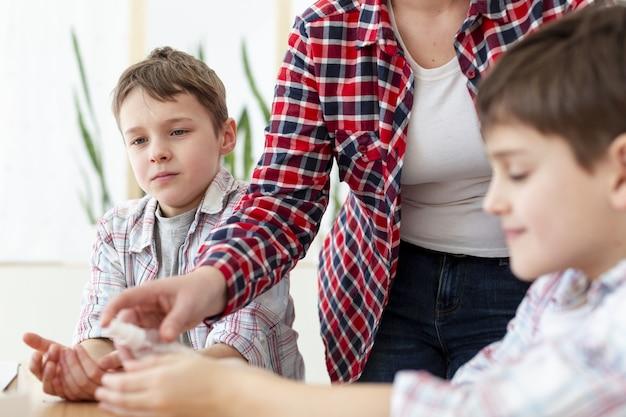 Madre che disinfetta le mani dei suoi figli