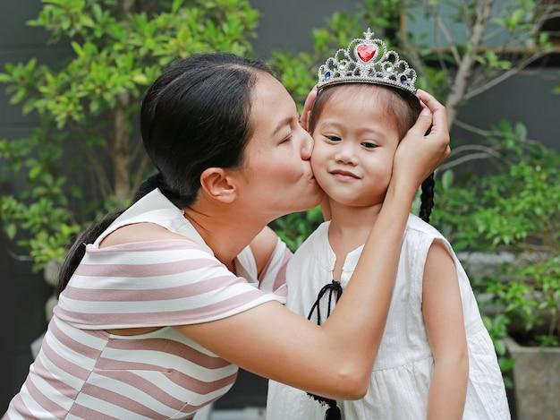 Madre che indossa la corona sulla testa della bambina e baci.