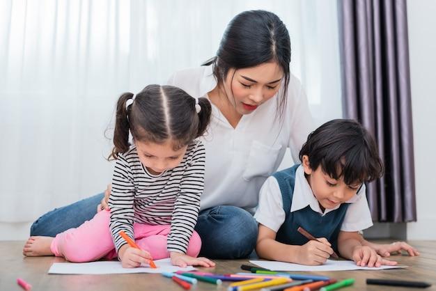 Madre che insegna ai bambini a disegnare classe. figlia e figlio che dipingono con colori a pastello