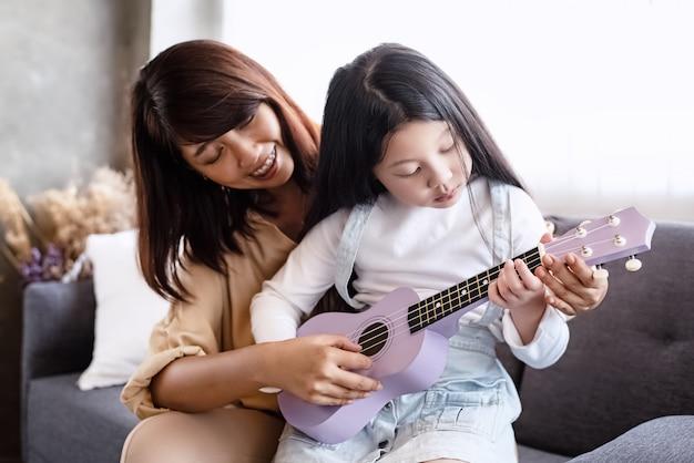 Madre che insegna alle ukulele con la bellissima figlia, nella sala della musica da studio, attività di famiglia, con sentimento felice
