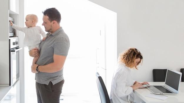 Madre che lavora al computer portatile a casa