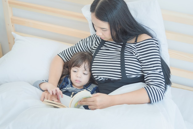 Madre che legge un libro di storia di tempo di letto a sua figlia in camera da letto.