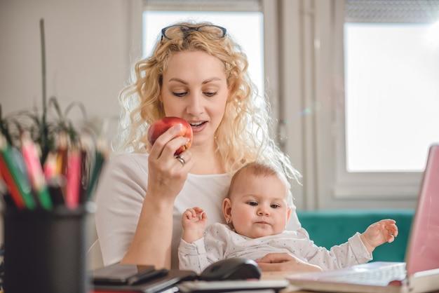 Madre che mangia l'ufficio della mela a casa