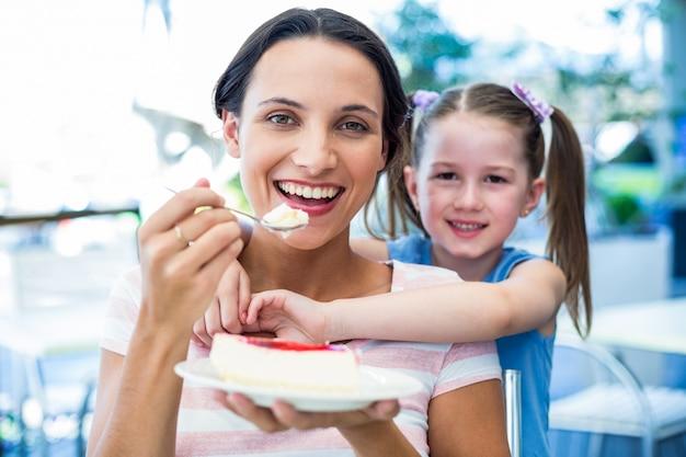 Madre che mangia una fetta di torta con sua figlia