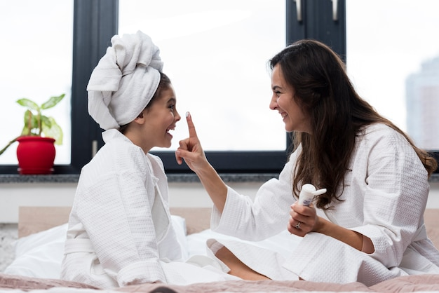 Madre che mette la crema per la cura della pelle sul viso delle sue figlie