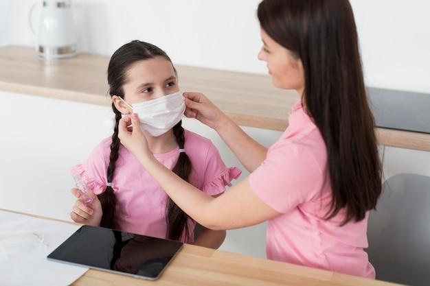 Madre che mette maschera sulla figlia