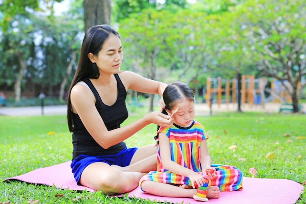 Madre che pettina i capelli della figlia che si trovano nel giardino verde.