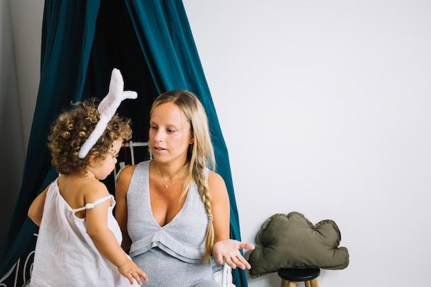 Madre che porta alla ragazza con orecchie da coniglio
