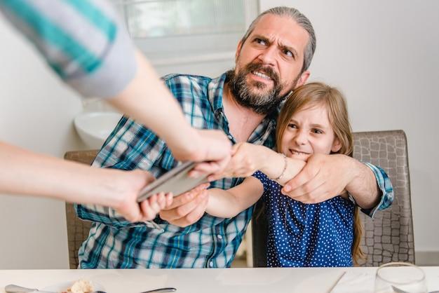 Madre che prende la compressa di digital a partire dalla figlia e dal padre