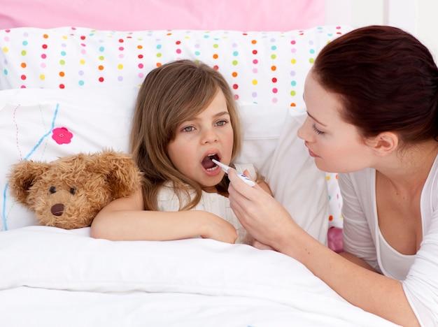 Madre che prende la temperatura di sua figlia con un termometro