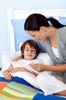 Madre che prende la temperatura di suo figlio
