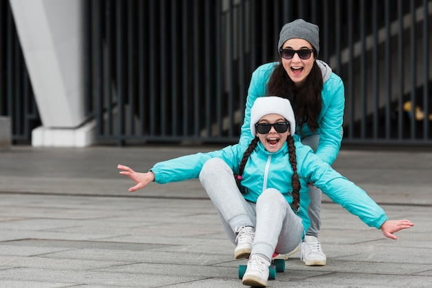 Madre che spinge ragazza su skateboard