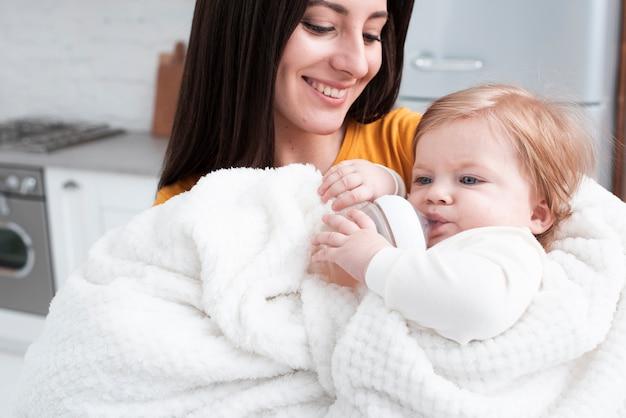 Madre che tiene bambino in soffice coperta