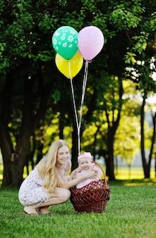 Madre con bambina su sfondo di alberi verdi.