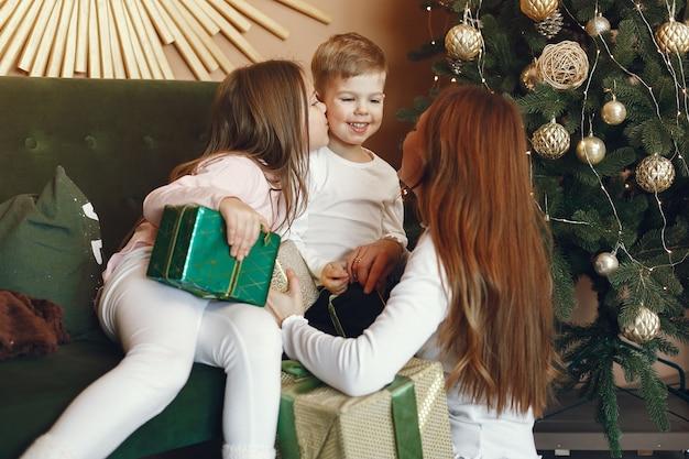 Madre con bambini carini vicino all'albero di natale
