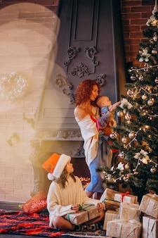 Madre con bambini che decora l'albero di natale