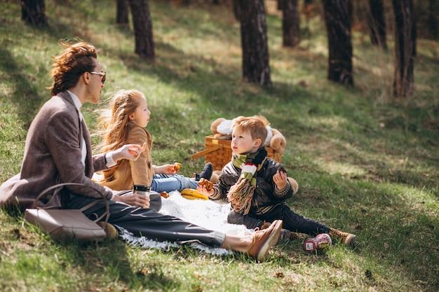 Madre con bambini che hanno picnic nella foresta