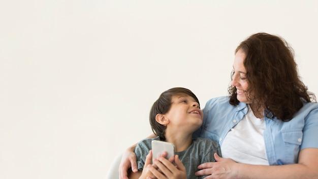 Madre con bambino alla ricerca di smartphone