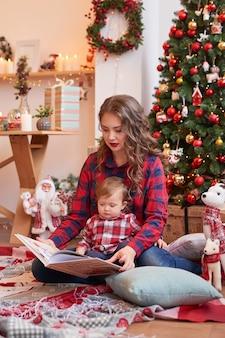 Madre con bambino in cucina decorato per natale.