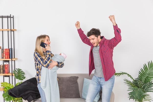 Madre con bambino parlando sul telefono vicino padre allegro
