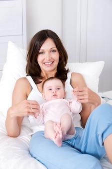Madre con bambino seduto a casa in casual
