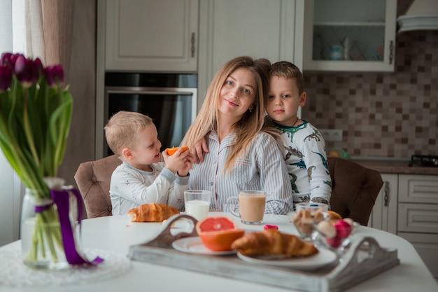 Madre con figli facendo colazione in cucina